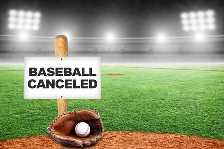 Baseball canceled sign on baseball bat stuck to the ground with glove and ball in empty stadium. Concept of baseball season canceled due to Covid-19, player strike; lockout, or breakdown in talks with players union.