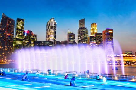 Small crowd of unidentifiable spectators watching a sea fountain at the Marina Bay with Singapore's downtown business district skyline in the background during sunset blue hour. 에디토리얼