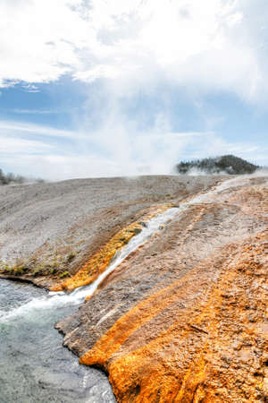 Hot water runoff from Excelsior Geyser flowing into the Firehole River at Yellowstone National Park's Midway Geyser Basin.