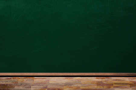 Education concept showing empty classroom chalkboard and wooden table with copy space.
