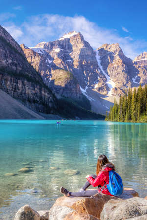 Girl enjoying the turquoise-colored Moraine Lake in the Canadian Rockies of Banff National Park near Lake Louise. The Valley of the Ten Peaks in the background.