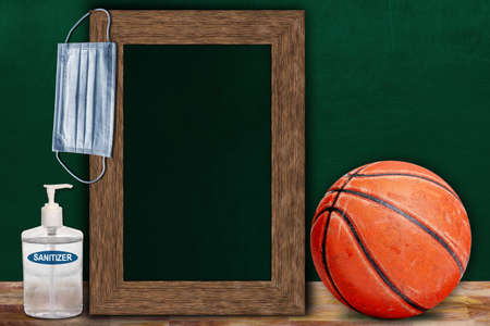 COVID-19 new normal sports concept in a classroom setting showing framed chalkboard with copy space and basketball on wooden table.