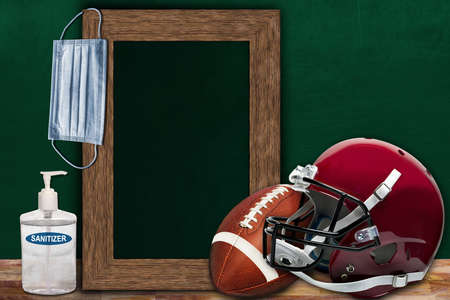 COVID-19 new normal sports concept in a classroom setting showing framed chalkboard with copy space and American football and helmet on wooden table.