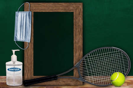 COVID-19 new normal sports concept in a classroom setting showing framed chalkboard with copy space and tennis racket and ball on wooden table.