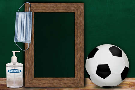 COVID-19 new normal sports concept in a classroom setting showing framed chalkboard with copy space and soccer ball on wooden table. Banque d'images