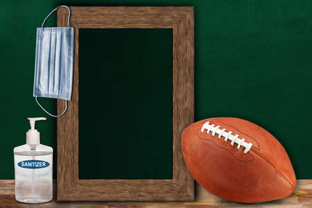 COVID-19 new normal sports concept in a classroom setting showing framed chalkboard with copy space and American football on wooden table.
