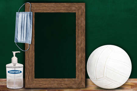 COVID-19 new normal sports concept in a classroom setting showing framed chalkboard with copy space and Volleyball on wooden table.