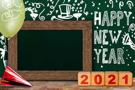 Happy New Year 2021 celebration with background chalkboard party theme and wooden frame copy space surrounded by balloon, party hat, confetti and wooden blocks. Banque d'images