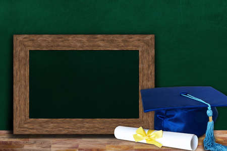 Education concept of graduation hat and diploma on wooden classroom table with copy space on blank photo frame for text.