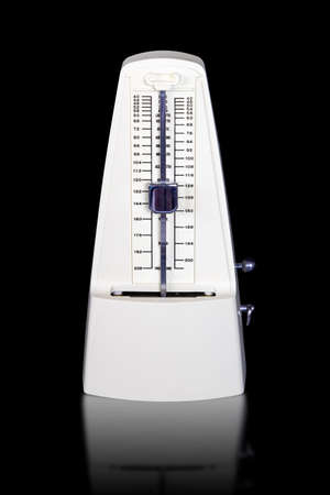White mechanical wind up metronome isolated on black background with reflections.