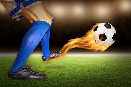 Soccer player kicking a fiery flaming football in flight at a stadium.