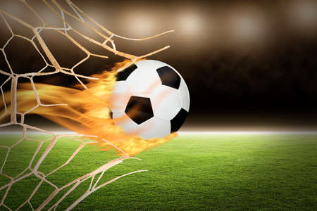 Fiery soccer ball with trailing flames through broken goal net with copy space.