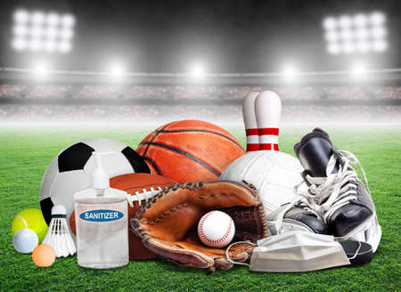 COVID-19 coronavirus new normal and sports concept showing sports equipment, rackets and balls with hand sanitizer and face mask inside stadium and copy space. Banque d'images