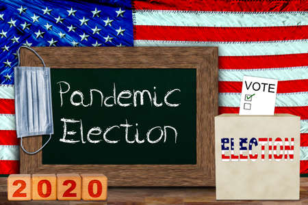 US pandemic elections concept with American flag hung behind wooden frame chalkboard for copy space, and ballot box with voter slip. Concept of voter risk and health concerns in a presidential, senate and house of representatives elections.