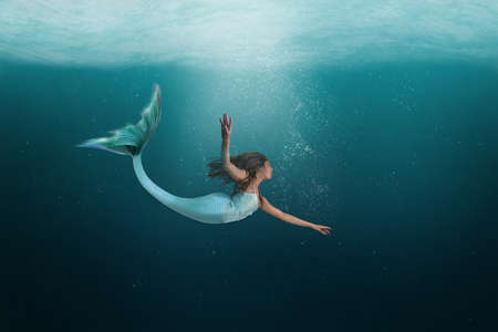 Mermaid with long tail swimming under the deep waters of the ocean.
