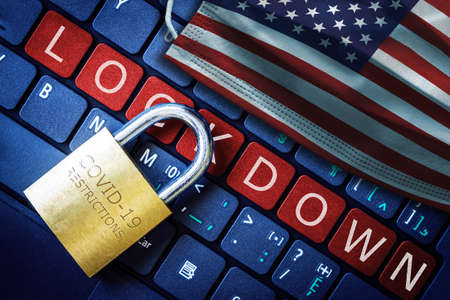 US COVID-19 coronavirus lockdown restrictions concept illustrated by padlock on laptop red alert keyboard buttons and face mask with American flag. Banque d'images