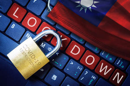 Taiwan COVID-19 coronavirus lockdown restrictions concept illustrated by padlock on laptop red alert keyboard buttons and face mask with Taiwanese flag.