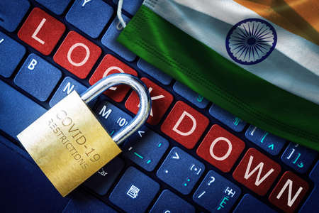 India COVID-19 coronavirus lockdown restrictions concept illustrated by padlock on laptop red alert keyboard buttons and face mask with Indian flag.