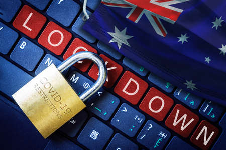 Australia COVID-19 coronavirus lockdown restrictions concept illustrated by padlock on laptop red alert keyboard buttons and face mask with Australian flag.