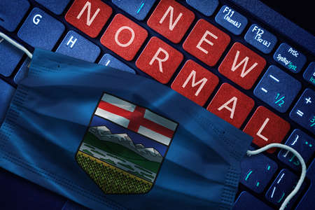 COVID-19 coronavirus new normal concept in the Canadian province of Alberta as shown by Alberta flag on face mask with New Normal on laptop red alert keyboard buttons.