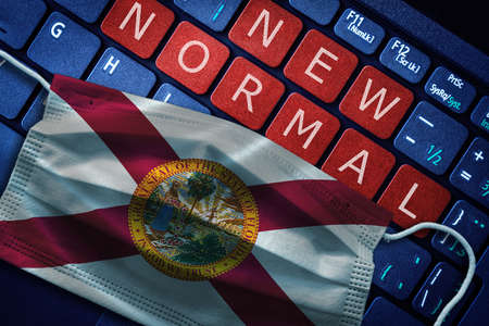 COVID-19 coronavirus new normal concept in the US state of Florida as shown by Florida flag on face mask with New Normal on laptop red alert keyboard buttons.