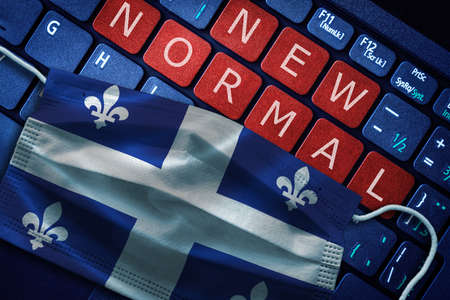 COVID-19 coronavirus new normal concept in the Canadian province of Quebec as shown by Quebec flag on face mask with New Normal on laptop red alert keyboard buttons.