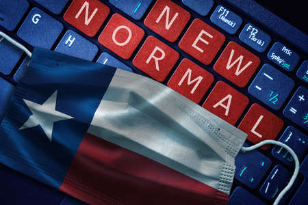 COVID-19 coronavirus new normal concept in the US state of Texas as shown by Texas flag on face mask with New Normal on laptop red alert keyboard buttons. Banque d'images