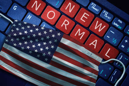COVID-19 coronavirus new normal concept in United States as shown by US flag on face mask with New Normal on laptop red alert keyboard buttons. Banque d'images