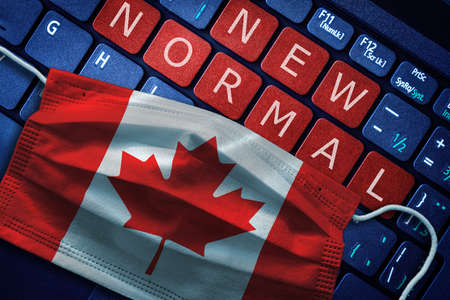 COVID-19 coronavirus new normal concept in Canada as shown by Canadian flag on face mask with New Normal on laptop red alert keyboard buttons.