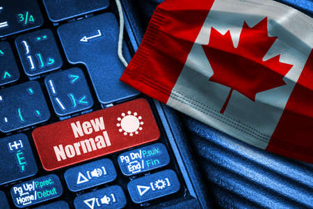 Concept of New Normal in Canada during Covid-19 with computer keyboard red button text and face mask showing Canadian Flag.