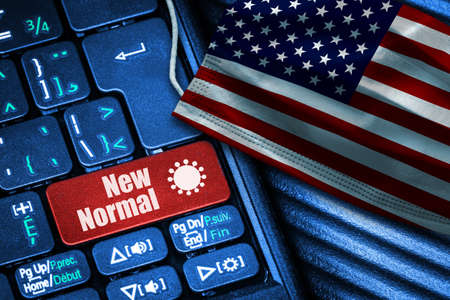 Concept of New Normal in the United States during Covid-19 with computer keyboard red button text and face mask showing US Flag. Banque d'images