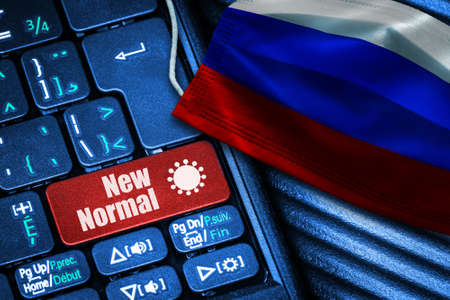 Concept of New Normal in Russia during Covid-19 with computer keyboard red button text and face mask showing Russian Flag.
