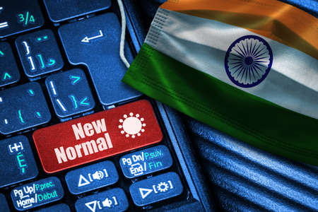 Concept of New Normal in India during Covid-19 with computer keyboard red button text and face mask showing Indian Flag.
