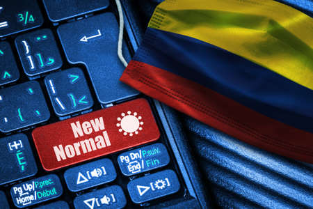 Concept of New Normal in Colombia during Covid-19 with computer keyboard red button text and face mask showing Colombian Flag. Banque d'images