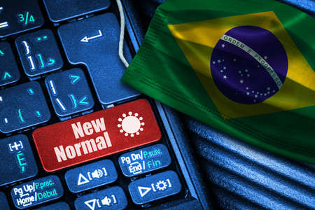 Concept of New Normal in Brazil during Covid-19 with computer keyboard red button text and face mask showing Brazilian Flag.