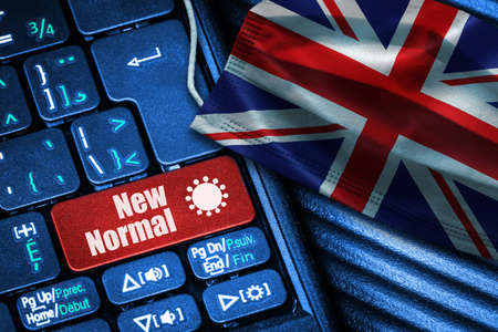 Concept of New Normal in United Kingdom during Covid-19 with computer keyboard red button text and face mask showing UK Flag. Banque d'images