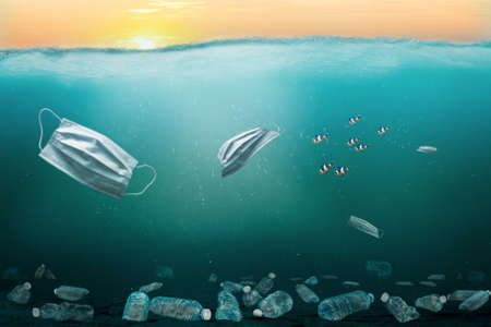 Ocean full of medical masks and plastic trash contributing to marine pollution problem. Surgical masks overuse during the COVID-19 coronavirus pandemic end up in oceans.