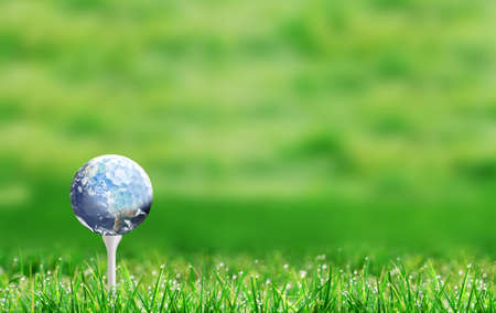 Planet earth golf ball on tee and with defocused bokeh golf course green background and copy space. Banque d'images