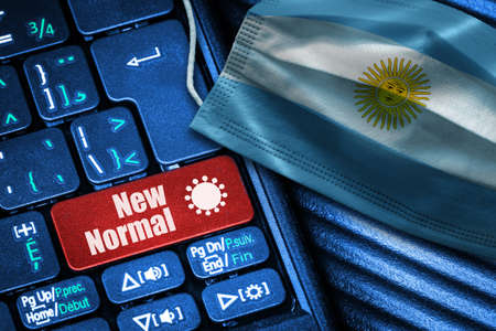 Concept of New Normal in Argentina during Covid-19 with computer keyboard red button  and face mask showing Argentinian Flag. Banque d'images