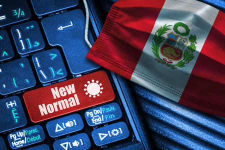 Concept of New Normal in Peru during Covid-19 with computer keyboard red button  and face mask showing Peruvian Flag.