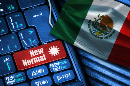 Concept of New Normal in Mexico during Covid-19 with computer keyboard red button  and face mask showing Mexican Flag.