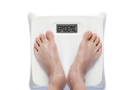 Feet on digital bathroom scale with the word OBESITY on screen.
