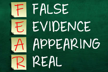 3D rendering of motivating and inspiring FEAR acronym on sticky notes posted to chalkboard meaning False Evidence Appearing Real.