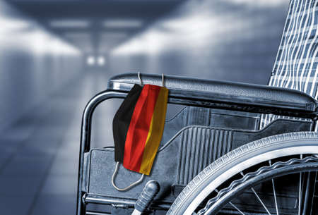Flag of Germany on face mask hanging on empty wheelchair in hallway of hospital or retirement nursing care home with copy space. Concept of COVID-19 pandemic in affecting seniors or elderly.
