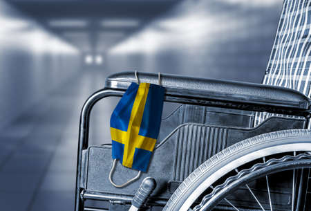 Flag of Sweden on face mask hanging on empty wheelchair in hallway of hospital or retirement nursing care home with copy space. Concept of COVID-19 pandemic in affecting seniors or elderly.