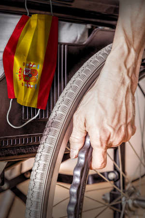 Elderly person in wheelchair at Spain nursing home with hanging Spanish flag face mask. Concept of Covid-19 coronavirus outbreak in nursing care homes or elderly retirement facilities.