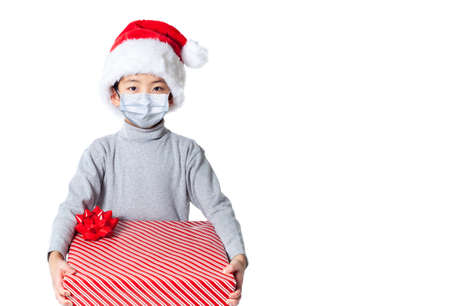LIttle boy receiving Xmas gift during Covid Christmas wearing Santa hat and face mask due to pandemic, isolated on white background with copy space.