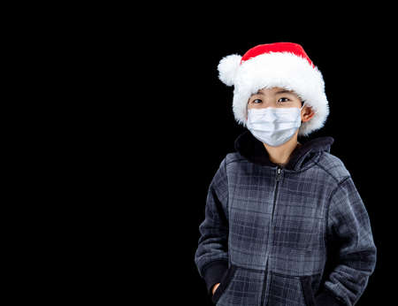 Cute boy during Covid Christmas wearing Santa hat and face mask due to pandamic, isolated on black background with copy space.