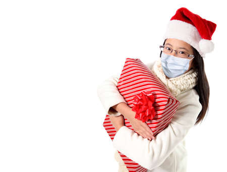 Young girl hugging Xmas gift during Covid Christmas wearing Santa hat and face mask due to pandemic, isolated on white background with copy space.