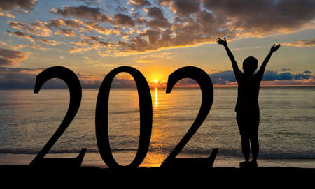New Year 2021 sunrise welcome by the beach with silhouette of woman with raised hands.